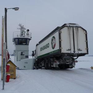 En fodertransport kör ner för rampen ombord på förbindelsefartyget Viken i Granvik i Pargas. Havet är nästan helt instäckt.