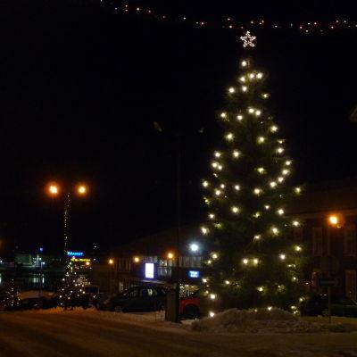En julgran lyser upp en mörk vinterkväll.