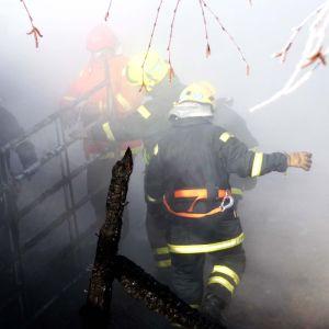 Flera brandmän går igenom rök och något som ser ut som ruinerna av en ladugård.