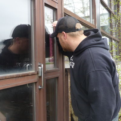 Markus Wilson tittar in genom fönstret i Närpesgården