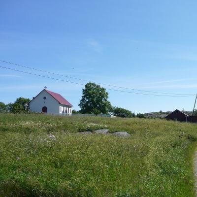 En skärgårdsby med en väg genom en äng och en vit kyrka i bakgrunden