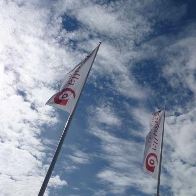Två avlånga vita flaggor med röd text: Kårkulla, vajar i en flaggstång en solig dag med moln.