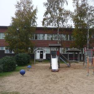 En lekpark framför en röd tegelbyggnad. Träd döljer delvis byggnadens fasad.