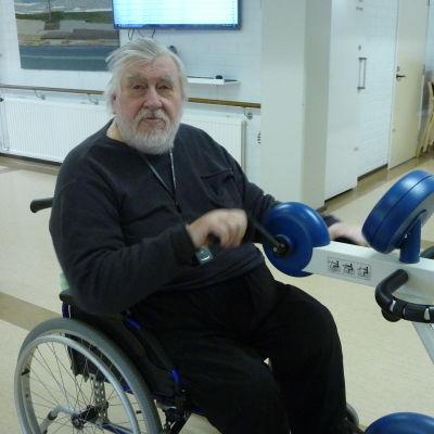 En äldre man sitter i rullstol.