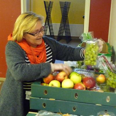 En blond kvinna står och plockar upp frukt ur en låda.