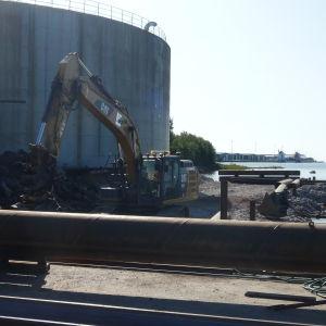 En grävmaskin gräver vid kajen i yttre hamnen i Kaskö.