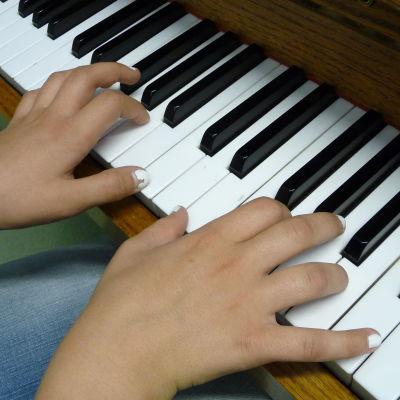 Tangenterna på ett piano, två händer spelar på tangenterna.