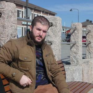 Amir sitter på en bänk i Kristinestad en solig vårdag.