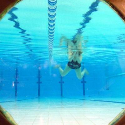 Simmare i vattnet i simhallen.