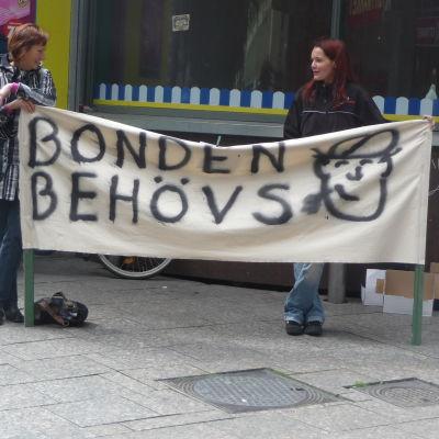 """Två kvinnor håller upp en banderoll som lyder """"bonden behövs""""."""