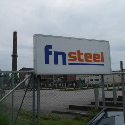 Skylt där det står Fnsteel med fabriksområdet i bakgrunden.