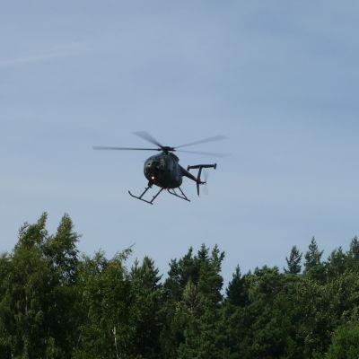 Helikopter flyger ovanför träden.