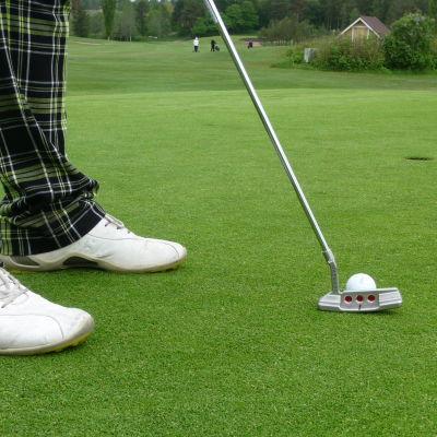 Golfklubba och boll på en green
