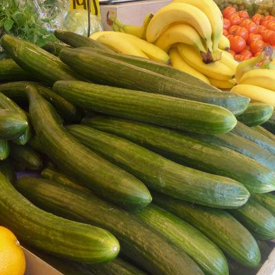 Gurkor, bananer och tomater på rad.