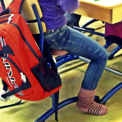 Skolväska och elev i skolbänken.
