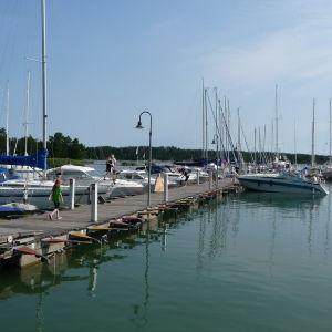 Två personer går på en brygga ut i Nagu gästhamn full med båtar mitt i sommaren.