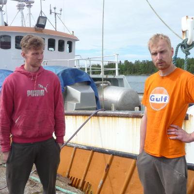 Axel Hellström och Jukka-Pekka Vironen står på kajen vid ett fiskefartyg.