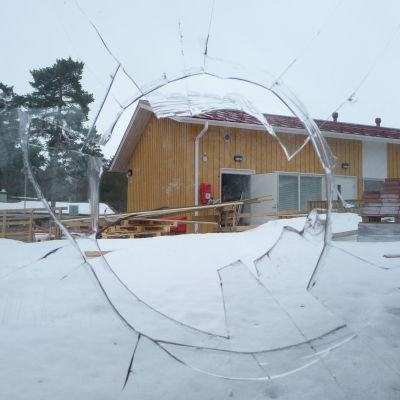 Utkik över en gård genom en krossad fönsterruta.