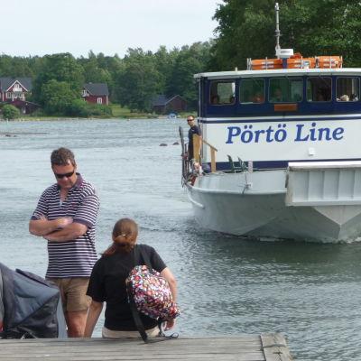 Mänskor på en brygga och båt i bakgrunden