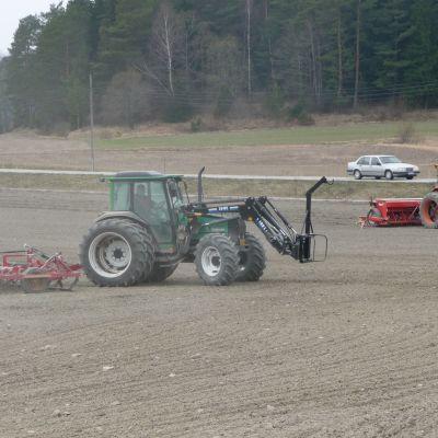 Traktorer på med harv och såmaskin på åkern