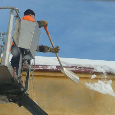 En man rensar taket från is och snö