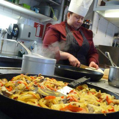Kokki valmistaa ruokaa ravintolassa.