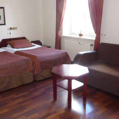 Ett anonymt hotellrum. Två sängar, en soffa och ett bord.