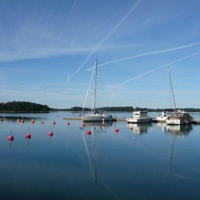Stiltje vid en hamn med några båtar förtöjda.
