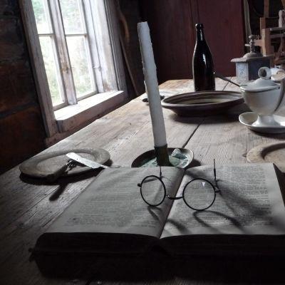 Gammalt stockbord inne i en stuga. På bordet står kärl, ett stearinljus, en bok och ett par glasögon.
