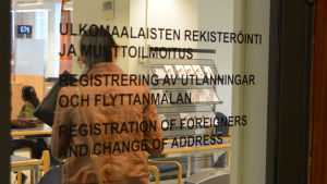 Vy in genom dörr på vilken det står registrering av utlänningar och flyttanmälan