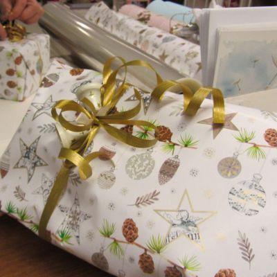 Kuvassa joulupaketti, jossa kultainennauha ja joulukelloja.