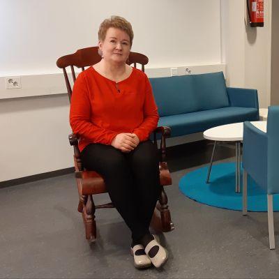 Palveluohjaaja Jaana Uotinen istuu keinutuolissa Sulkavan uudessa olohuoneessa.