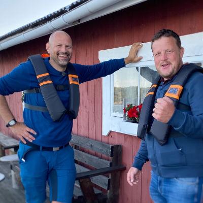 Matias och Micke står vid ett rött båthus med flytvästarna på.