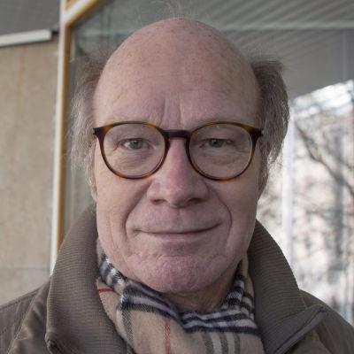 Bild på man i glasögon och brun jacka.