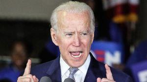 Biden puhuu osoittaen sormillaan ylöspäin. Hänellä on tummansininen puku. Taustalla näkyy Bidenin kannattajia.