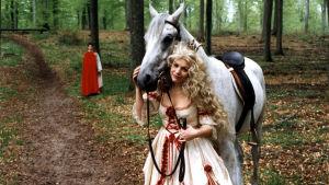 En blond flicka står vid sidan och håller en vit häst.
