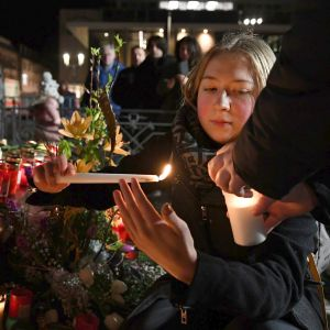 En kvinna tänder ett ljus vid minnesplatsen.