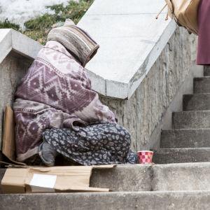 Kvinna sitter i en trappa utomhus och tigger. En annan kvinna går förbi.
