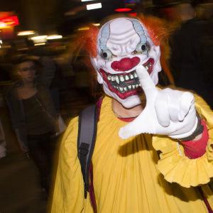 En person utklädd till en skrämmnade clown. Gul dräkt, rött hår och förvridet ansikte.