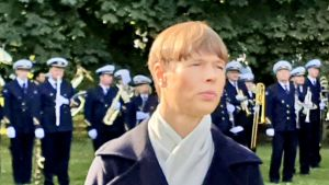 Estlands president med en orkester i bakgrunden.