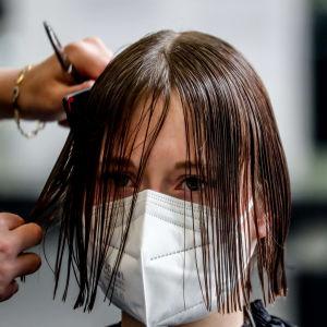 En person med munskydd har vått hår och en frisör klipper personens hår.