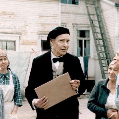 Valokuvaaja Hurme (Toivo Mäkelä) naurattaa pihan naisia elokuvassa Aika hyvä ihmiseksi (1977).