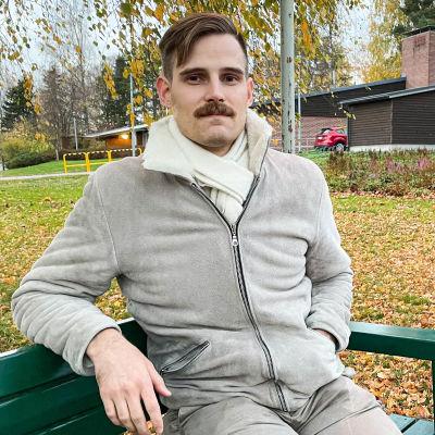 En man som sitter på en bänk.