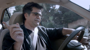 Mies ajaa autoa.