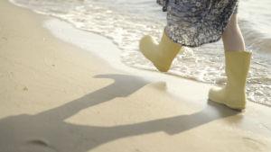 barnfötter i gula stövlar går på strand