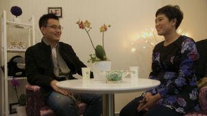 Ett kinesiskt par på blinddejt sitter vid ett vitt bord.