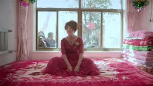 En kinesisk kvinna i röd bröllopsklänning sitter på en säng. I bakgrunden kikar nyfikna in genom fönstret.