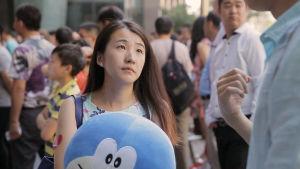 En kvinna på ett kinesiskt dejtingevenemang ser upp mot en man som talar.