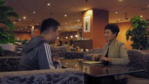 Ett kinesiskt par på blinddejt sitter vid ett cafébord. Kvinnan är prydligt klädd, mannen är klädd i träningsoverall.