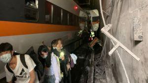 Ett söndrigt tåg inne i en tunnel. På sidan av tåget syns människor som lungt tar sig ut ur tunneln.